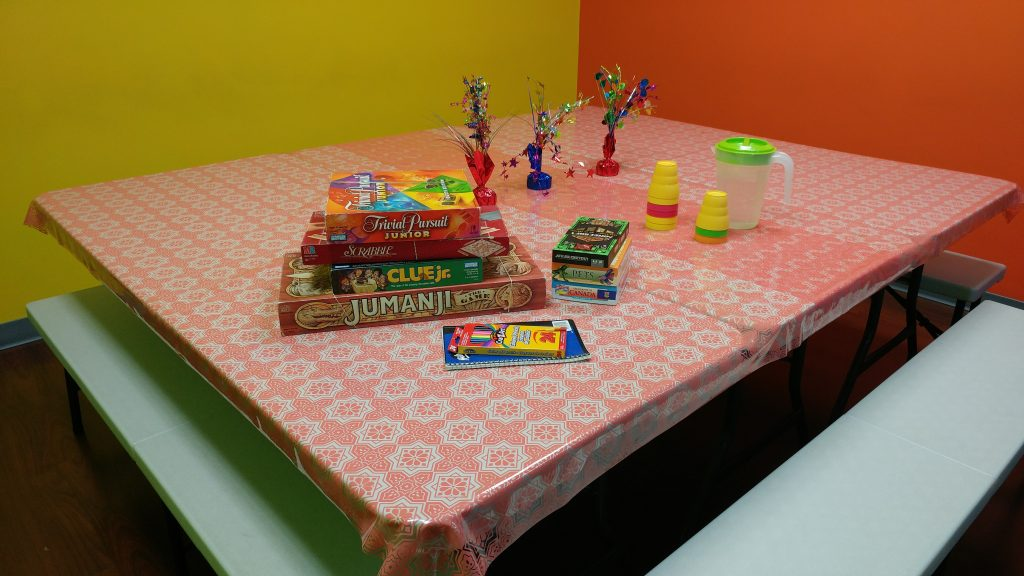 stack of games on a table in a room with colourful walls