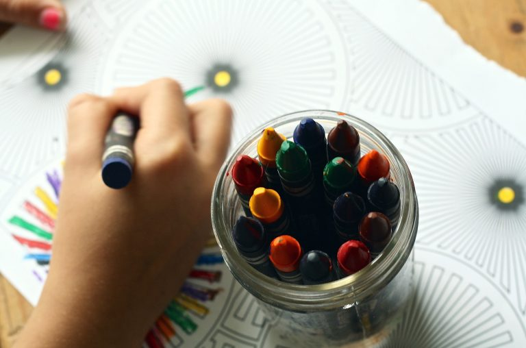 child coloring with a crayon and a jar of crayons next to hand